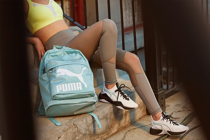 Selena Gomez Presents Puma's New Defy Sneaker tan leggings yellow sports bra white sneakers teal backpack